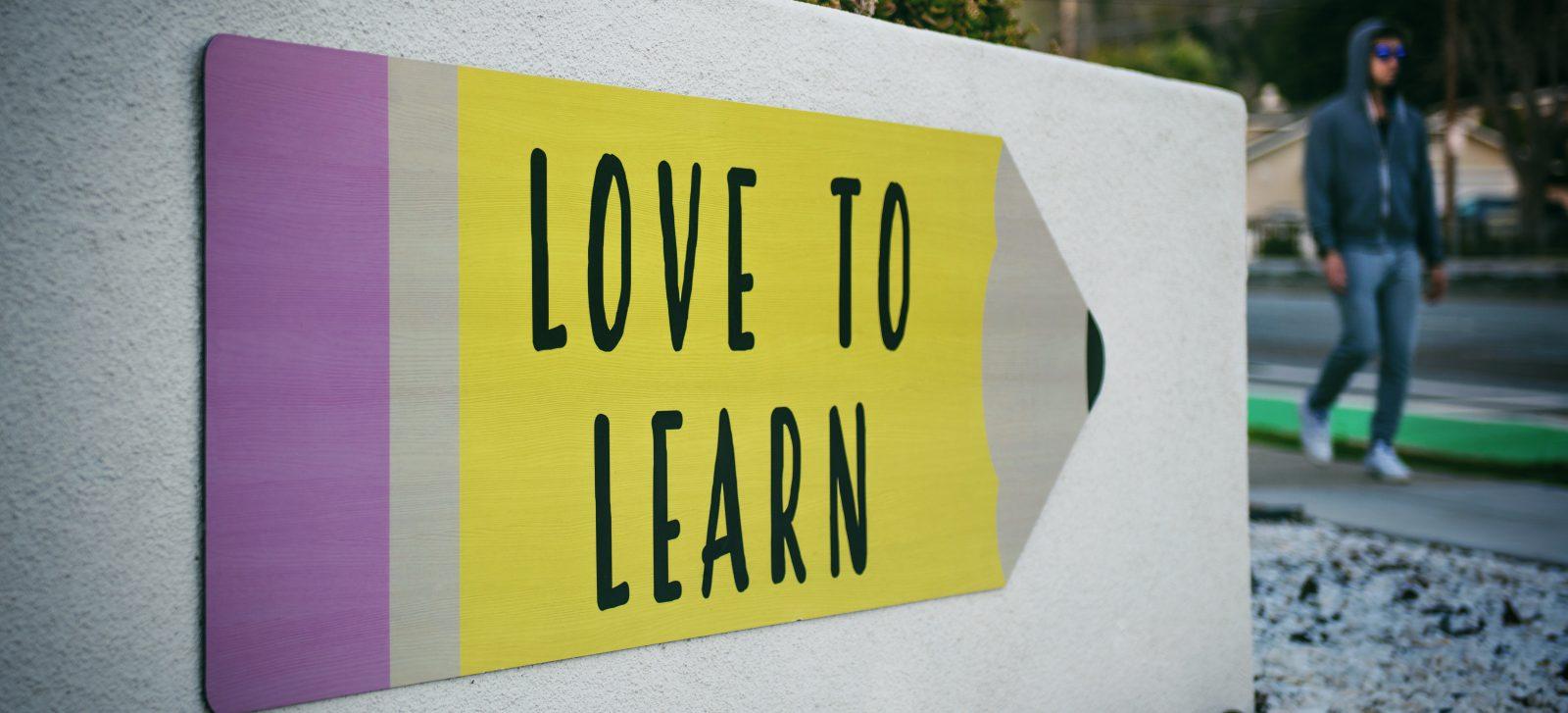 """tecniche per scrivere: un cartello con una matita che riporta la frase """"love to learn"""""""
